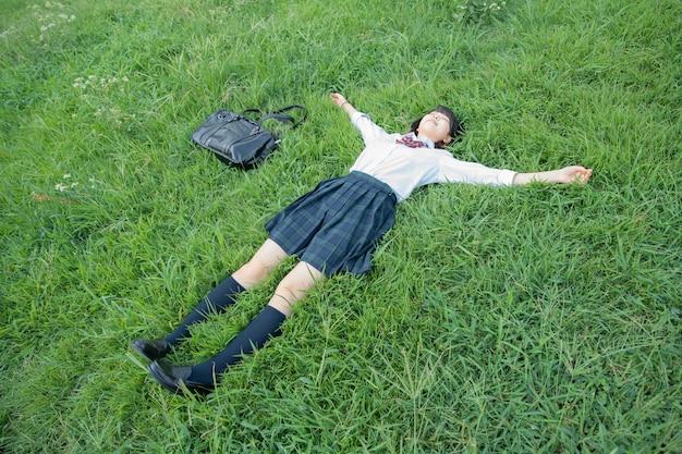 High school girl tumbado en el césped