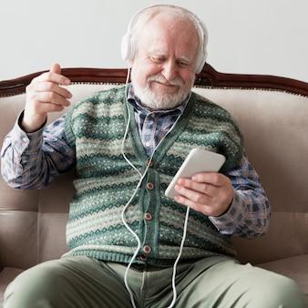 Higha ngle senior en el sofá tocando canciones