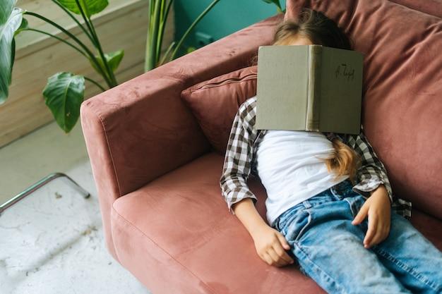 Highangle vista de niño cansado y soñoliento niña acostada en un sofá suave con libro de papel en la cabeza en casa