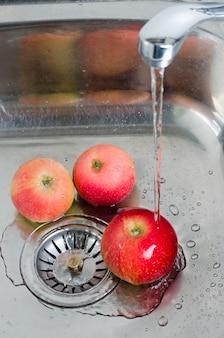 Higiene alimenticia. tres manzanas rojas en un fregadero de metal bajo un chorro de agua. foto vertical