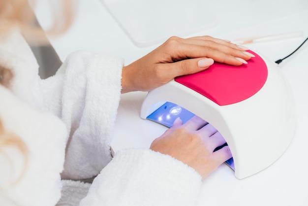 Higiene y cuidado de las uñas secando el esmalte de uñas