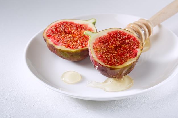 Higos cortados en trozos y rociados con miel en un plato blanco. vitamina comida sana orgánica