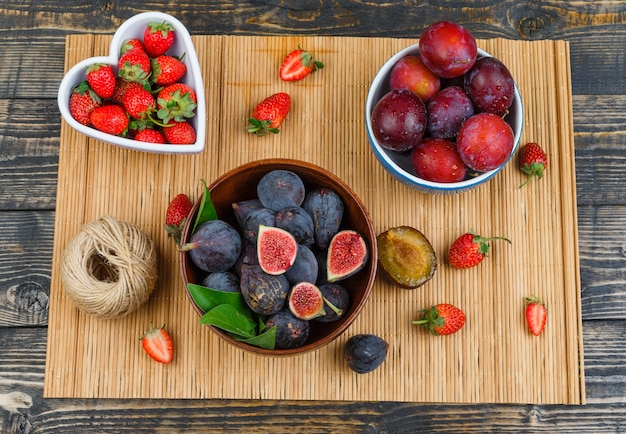 Higos, fresas y ciruelas en mesa de madera