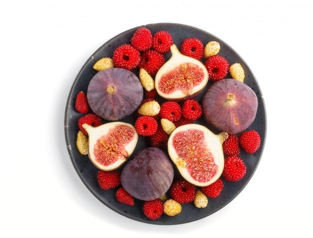 Higos, fresas y frambuesas frescas en la placa de cerámica azul aislada en blanco. vista superior
