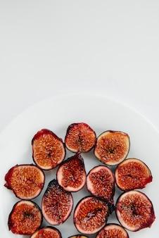 Higos maduros y dulces cortados y dispuestos en un plato sobre un fondo blanco con espacio libre. frutas y vegetarianismo.