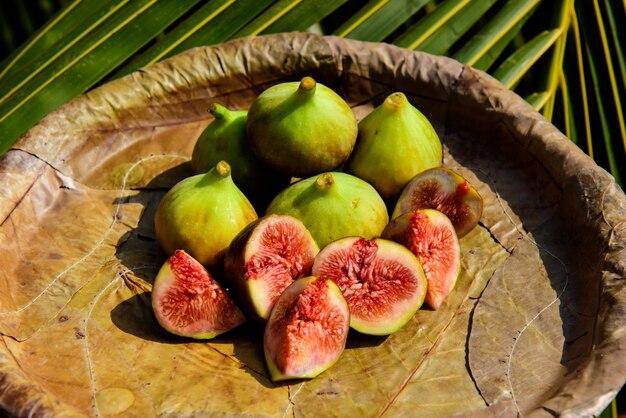 Higos maduros en un plato de hojas de cerca. frutas tropicales frescas: higos dulces en rodajas