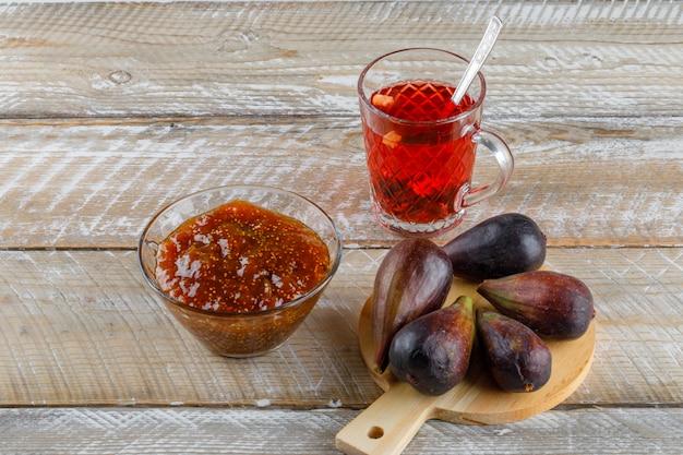 Higos con taza de té, mermelada de higos vista de ángulo alto en madera y tabla de cortar