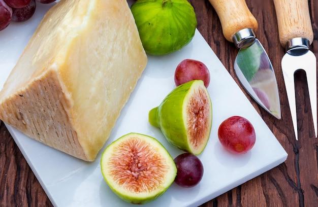 Higos, uvas rojas y queso de oveja (tipo manchego). sobre mármol blanco y madera.