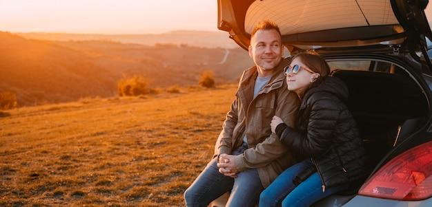Hija abrazando al padre mientras está sentado en el baúl de un automóvil