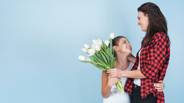 Hija abrazando a la madre y dándole tulipanes blancos