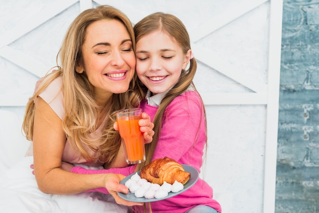 Hija abrazando a la madre con el desayuno en la cama