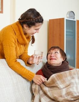 Hija adulta cuidando de madre enferma