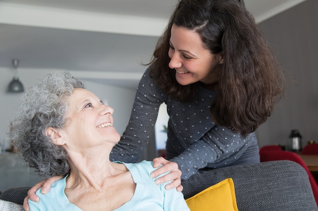 Hija adulta feliz visitando anciana madre