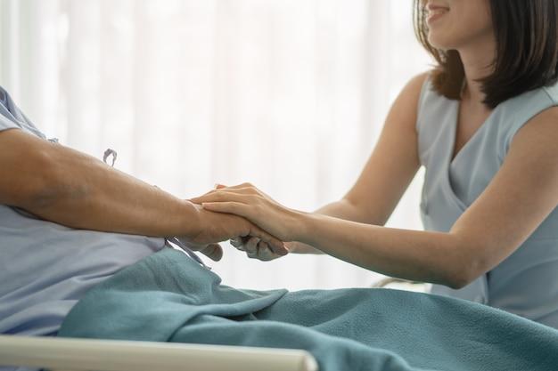 Hija adulta que toca las manos de su padre y anima a combatir el cáncer en el hospital
