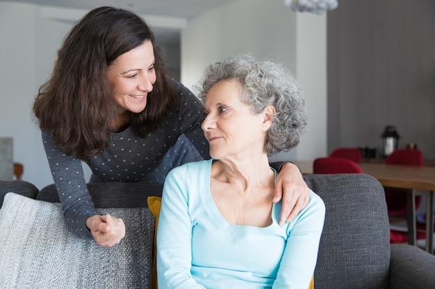 Hija adulta sonriente que apoya a la madre mayor triste
