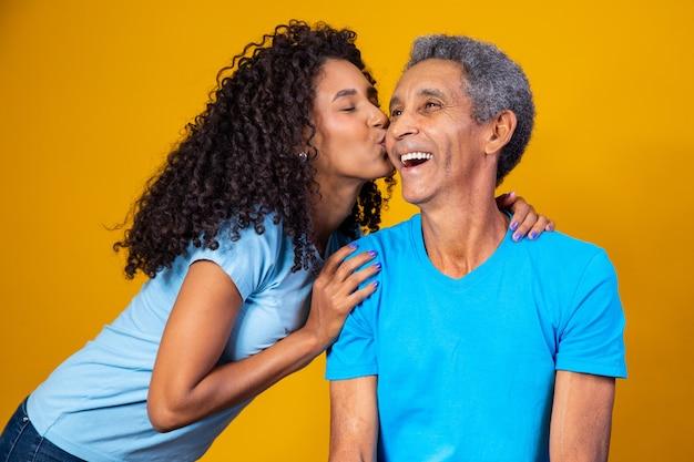 Hija afro besando la mejilla de su padre mayor. concepto del día del padre