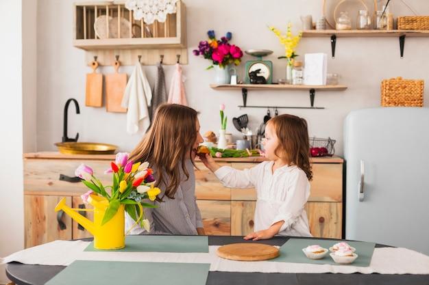 Hija alimentando a la madre con cupcake