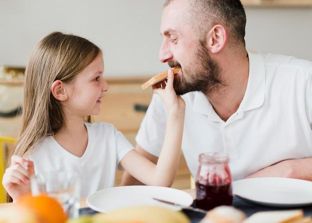 Hija alimentando a papá el día del padre
