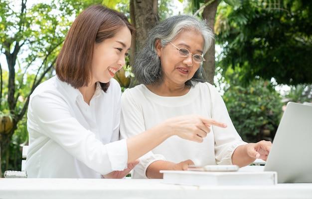 Hija asiática enseñando a anciana a usar las redes sociales en línea en la computadora portátil después de la jubilación.