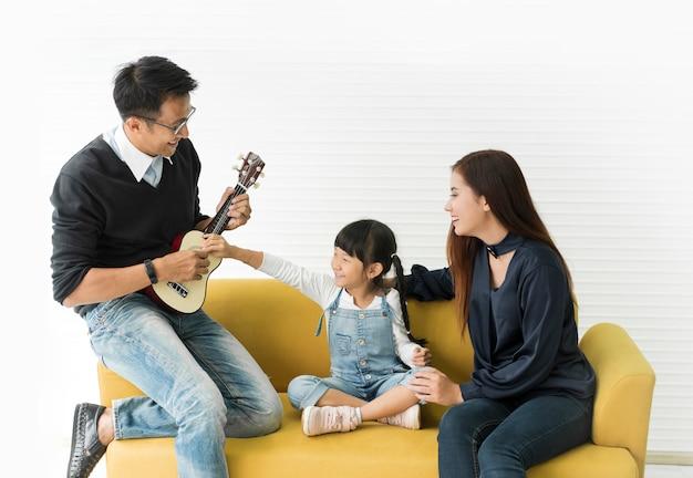 Hija asiática que toca la guitarra y que canta con el padre y la madre en el sofá en sala de estar.