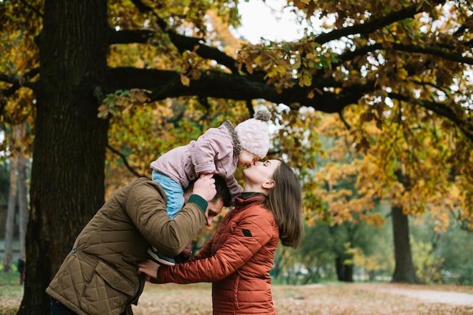 Hija besando a la madre del cuello del padre en el bosque de otoño