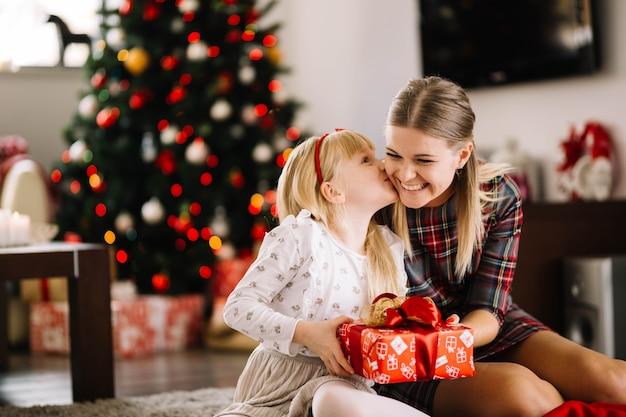 Hija besando madre en navidad