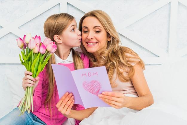 Hija besando a madre con tarjeta de felicitación