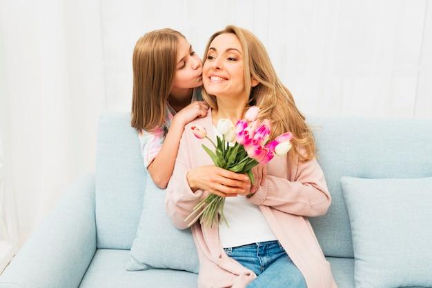 Hija besándose feliz madre con flores