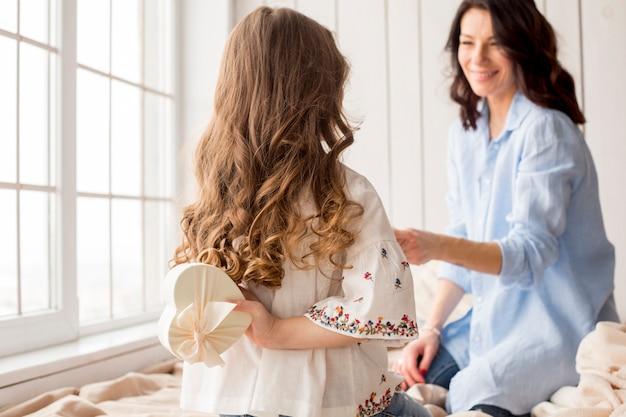 Hija con caja de regalo detrás de la espalda para madre