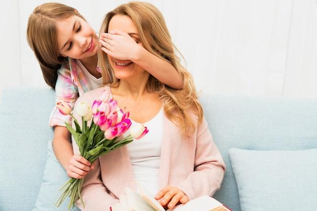 Hija cerrando los ojos madre y regalando flores.