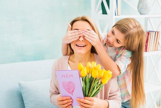 Hija cerrando ojos madre con regalos.