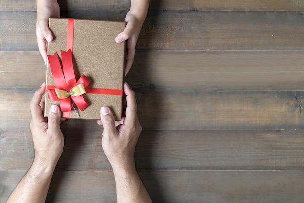 Hija cogidos de la mano de papá dando caja de regalo actual
