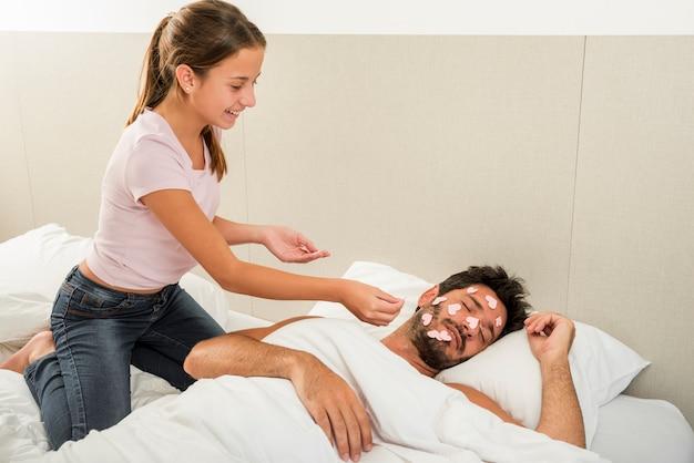 Hija colocando corazones en padre durmiendo