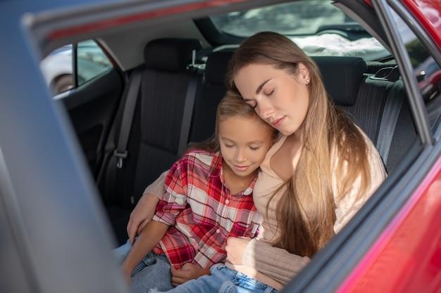 Hija complacida y su mamá abrazándose, tomando una siesta en el asiento trasero del auto