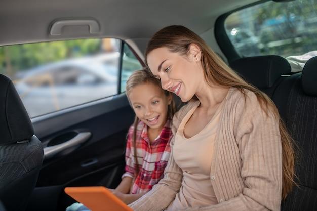 Hija complacida y su mamá revisando algo en la tableta en el asiento trasero del coche