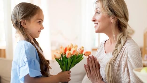 Hija dando a madre ramo de tulipanes como regalo
