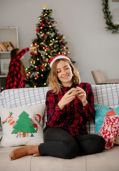 Hija decorando el árbol de navidad y la madre con gorro de papá noel sentado en el sofá y disfrutando de la navidad en casa