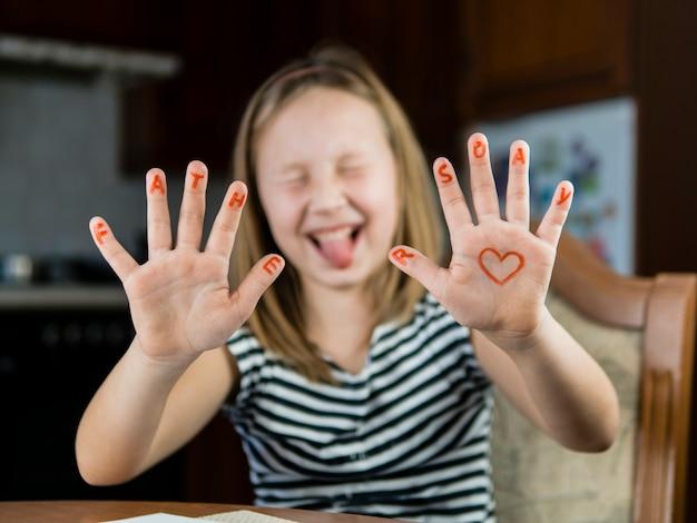 Hija dibujando un corazón en su mano para el día del padre
