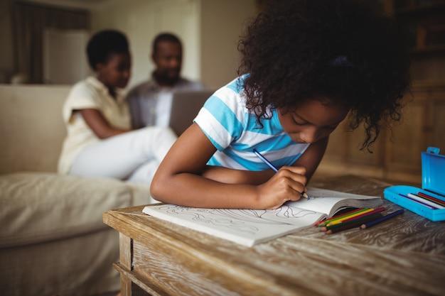 Hija dibujando en el libro mientras los padres usando la computadora portátil en segundo plano.