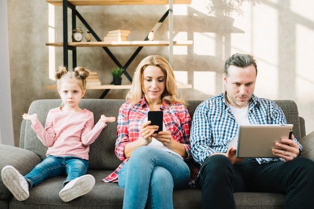 Hija enojada que se sienta en el sofá con su madre y padre que usa la tableta digital; celular en casa