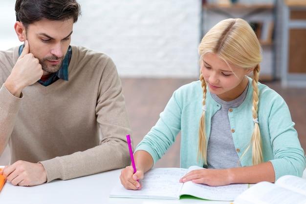 Hija escribiendo y padre está mirando
