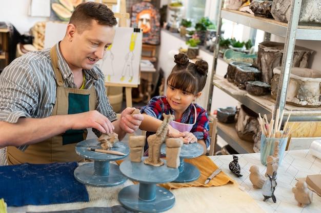 Hija esculpir animales de arcilla con el padre que trabaja en la escuela de arte
