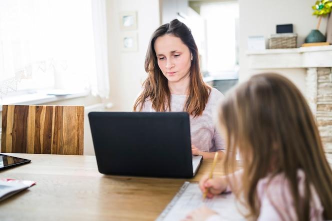 Hija estudiando n frente a su madre usando laptop