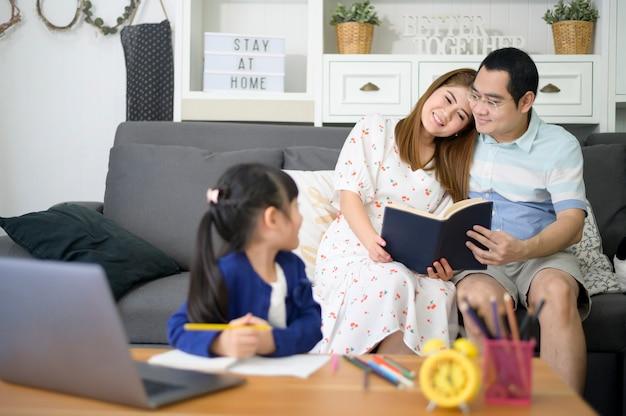 Hija feliz asiática está usando la computadora portátil para estudiar en línea a través de internet mientras los padres están sentados en el sofá en casa. concepto de e-learning