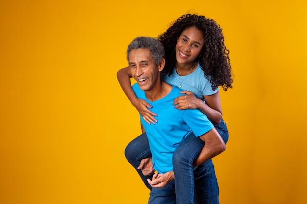 Hija feliz en la espalda del padre sobre fondo amarillo.