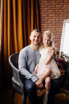 Hija feliz de la familia que abraza a papá y se ríe en día de fiesta