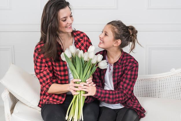 Hija feliz que da tulipanes a la madre en el sofá
