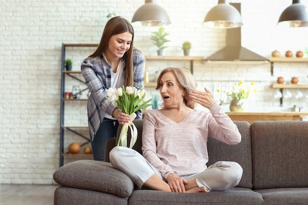 Hija feliz saludando a su madre con ramo de flores en casa