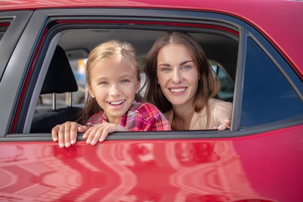 Hija feliz y su mamá mirando por la ventana en el asiento trasero del coche