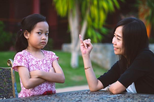 La hija fruncida el ceño está enojada y la madre se disculpó por mostrar su dedo meñique.